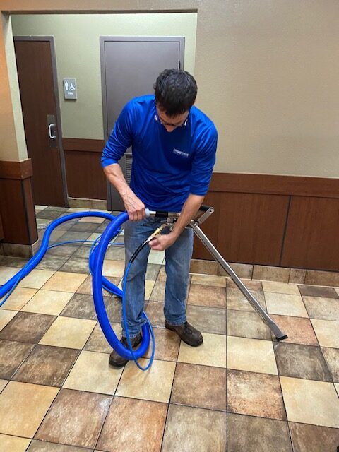 An employee cleaning the floor of a restaurant - Showcase Clean